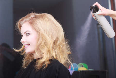 hairspray: Girl with blond wavy hair by hairdresser. Hairstylist with hairspray and female client. Young woman in hairdressing beauty salon. Hairstyle. Stock Photo