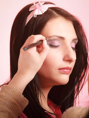 hairband: Female beauty. Makeup artist stylist applying with brush violet purple eyeshadow on eyelid of young woman on pink. Girl by visagiste.