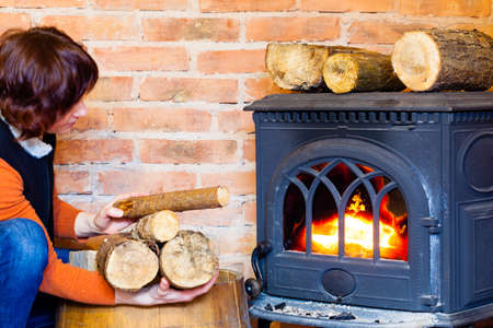 Winter at home. Woman putting some more wood on fire fireplace. Heating.