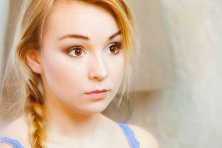 trenzas en el cabello: Retrato sincero de una mujer joven pensativa con el pelo trenzado rubio. La cara de pensativo adolescente. Cubierta. Foto de archivo