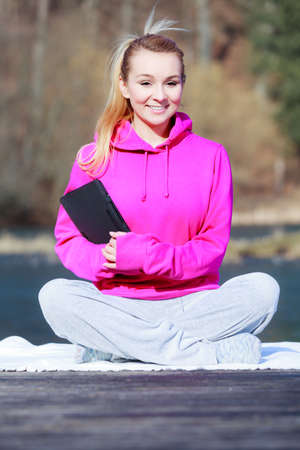 Full length of fitness woman sport teenage girl in tracksuit using tablet touchpad computer sitting on pier outdoor. Electronic technology. Stock Photo