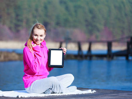sweatsuit: Full length of fitness woman sport teenage girl in pink tracksuit showing blank copy space screen of tablet touchpad computer sitting on pier outdoor. Electronic technology.