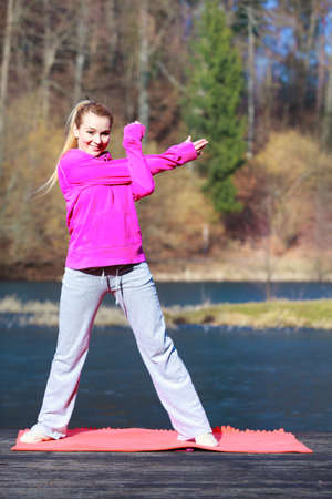 sweatsuit: Full length of young woman teenage girl in pink tracksuit doing morning exercise on mat on pier outdoor. Healthy active lifestyle.