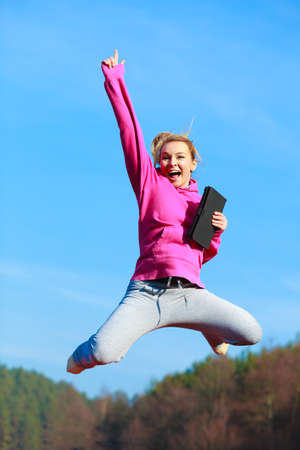 sweatsuit: Full length of cheerful fitness woman sport teenage girl in pink tracksuit jumping with tablet touchpad computer outdoor. Electronic technology.
