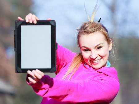 sweatsuit: Fitness woman sport teenage girl in pink tracksuit showing blank copy space screen of tablet touchpad computer outdoor. Electronic technology.