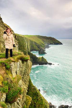 co cork: Irish atlantic coast  Woman tourist standing on rock cliff by the ocean Co  Cork Ireland Europe  Beautiful sea landscape natures beauty