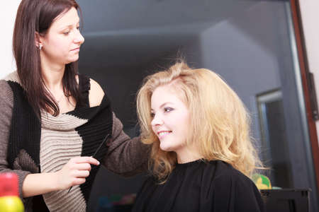Beautiful smiling girl with blond wavy hair by hairdresser  Hairstylist combing female client  Young woman in hairdressing beauty salon  Hairstyle