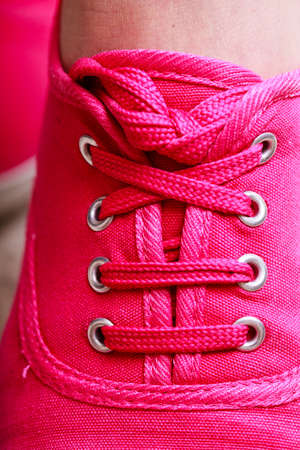 plimsoll: Closeup of casual vibrant pink sneakers plimsolls shoes boots on female feet. Sport fashion. Stock Photo