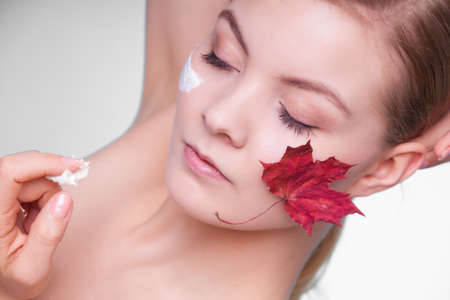 capillary: Skincare habits. Face of young woman with leaf as symbol of red capillary skin on gray. Girl taking care of her dry complexion applying moisturizing cream. Beauty treatment. Stock Photo
