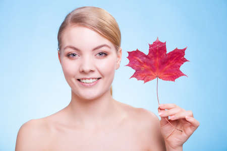 capillary: Skincare habits. Portrait of young woman with leaf as symbol of red capillary skin on blue. Face of girl taking care of her dry complexion. Studio shot. Stock Photo