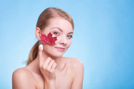 capillary: Skincare habits. Face of young woman with leaf as symbol of red capillary skin on blue. Girl taking care of her dry complexion applying moisturizing cream. Beauty treatment.