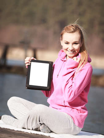Full length of fitness woman sport teenage girl in pink tracksuit showing blank copy space screen of tablet touchpad computer sitting on pier outdoor. Electronic technology. photo