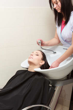 Hairstylist hairdresser washing customer hair  Brunette girl young woman relaxing in hairdressing beauty salon Stock Photo - 26556172