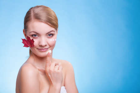 anti season: Skincare habits  Face of young woman with leaf as symbol of red capillary skin on blue  Girl taking care of her dry complexion applying moisturizing cream  Beauty treatment
