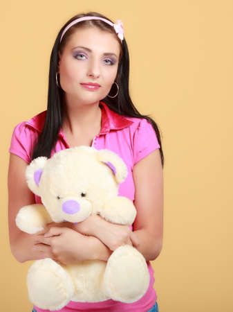 Portrait of childish young woman with headband holding toy. Infantile girl in pink hugging teddy bear on orange. Longing for childhood. Studio shot. photo