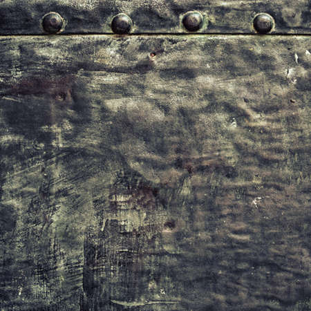 Closeup of grunge black metal plate with rivets and screws as background or texture  Square format  photo