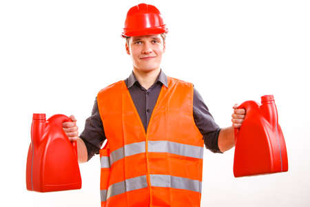 Young man construction worker in orange safety vest and red hard hat holding plastic canisters isolated on white. Industrial power and energy. Studio shot. photo