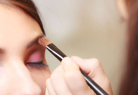 visagiste: Female beauty. Makeup artist stylist applying with brush cosmetic on eyebrow of young woman. Girl by visagiste. Stock Photo