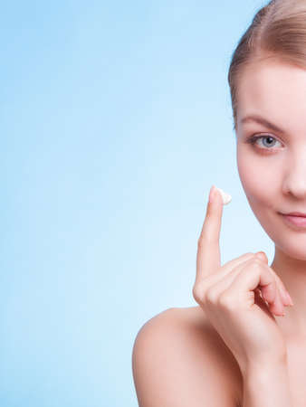 anti season: Girl taking care of her dry complexion applying moisturizing cream