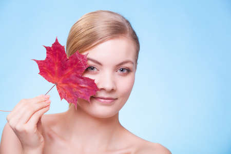 capillary: Portrait of young woman with leaf as symbol of red capillary skin on blue