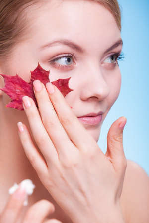 capillary: Face of young woman with leaf as symbol of red capillary skin on blue