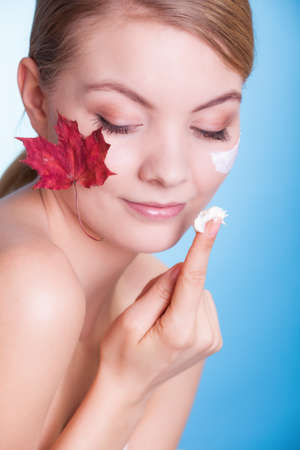 Face of young woman with leaf as symbol of red capillary skin on blue applying moisturizing cream photo