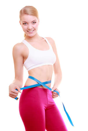 Young fitness woman fit girl with measure tape measuring her waistline isolated on white photo