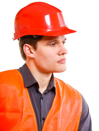 Young man construction worker builder foreman in orange safety vest and red hard hat isolated on white. Safety in industrial work. Studio shot. photo