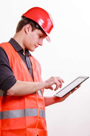 Jeune homme constructeur de travailleur de la construction dans le gilet de s�curit� orange et casque rouge aide de la tablette tactile isol� sur fond blanc. Technologie dans le travail industriel. Studio photo.