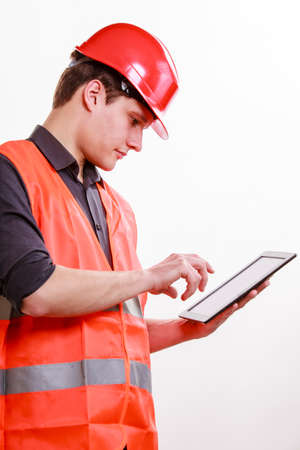 Young man construction worker builder in orange safety vest and red hard hat using tablet touchpad isolated on white. Technology in industrial work. Studio shot.