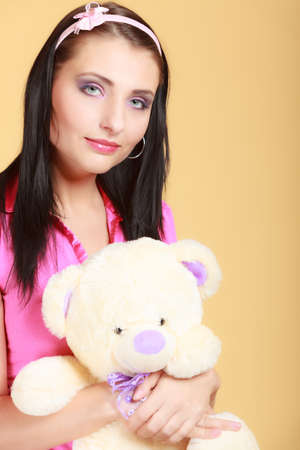 hairband: Portrait of childish young woman with headband holding toy. Infantile girl in pink hugging teddy bear on orange. Longing for childhood. Studio shot.