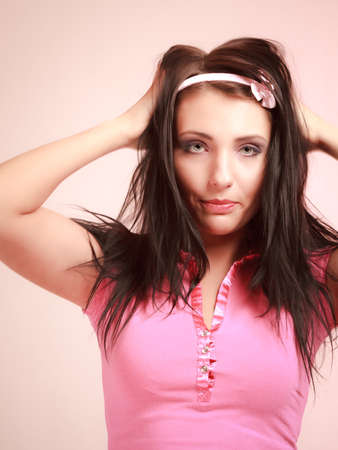 longing: Portrait of childish young woman with headband. Infantile girl messing up her hair on pink. Longing for childhood. Studio shot. Stock Photo