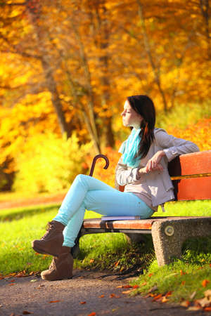 Fall lifestyle concept, harmony freedom  Casual young woman girl relaxing in autumnal park sitting on bench with book  Golden colorful leaves background photo