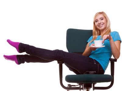 リラックスできる椅子の上に座って美しい少女女子大生茶またはコーヒーの分離した白い背景の上のカップを保持します。 写真素材