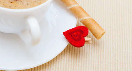 White cup of hot beverage drink coffee cappuccino latte with froth, sweet waffle roll stick with cream and red heart love symbol  Valentine s day  Studio shot   photo
