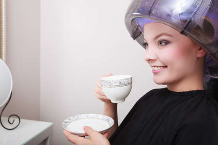 hot rollers: Young woman female client drinking hot drink coffee tea in hairdressing beauty salon  Girl in hair rollers curlers with hairdryer dryer relaxing by hairdresser hairstylist