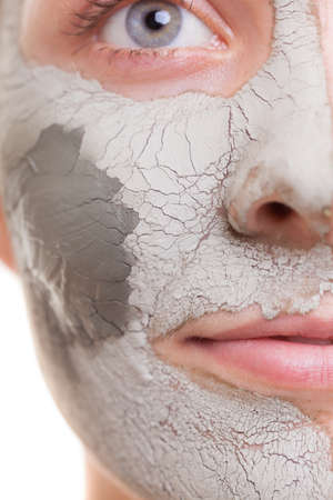 Skin care. Closeup of female face. Young woman applying clay mask. Girl taking care of her dry compexion. Isolated. Spa and beauty treatment.