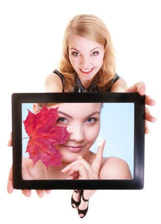 Happy blond girl showing photo of woman with red leaf and moisturizing cream. Modern young businesswoman holding tablet touchpad recommending care of dry skin. Isolated. Technology and beauty. photo