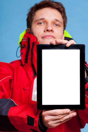 Man in red wind jacket holding  blank copy space. Guy showing screen tablet touchpad. Technology advertisement. photo