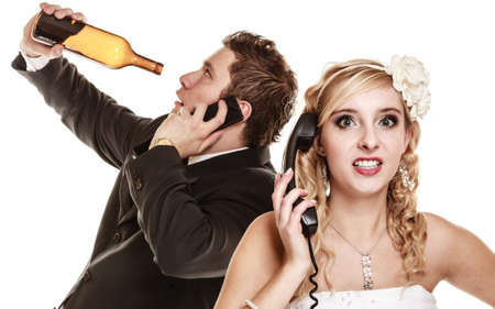 Wedding relationship difficulties. Angry woman and drunk man talking on the phone. Couple bride and groom quarelling isolated on white. Addiction and alcoholism. photo
