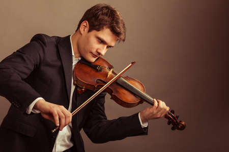 Art and artist. Young elegant man violinist fiddler playing\ violin on brown. Classical music. Studio shot.