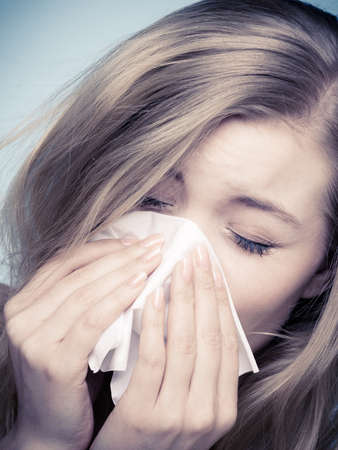 allergens: Flu cold or allergy symptom. Sick young woman girl sneezing in tissue on blue. Health care. Studio shot.