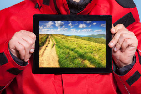 Closeup of male hands holding touchpad with photo of mountains. Man traveler showing screen tablet touchpad dreaming about adventure trip. Technology and travel. photo