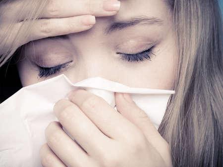 Gripe frío o síntomas de la alergia. Primer de la chica joven enfermo con fiebre estornudos en el tejido. Cuidado de la salud. Estudio de un disparo. Foto blanco y negro.