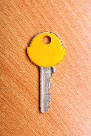 house coats: House key with yellow plastic coats caps on wooden table .
