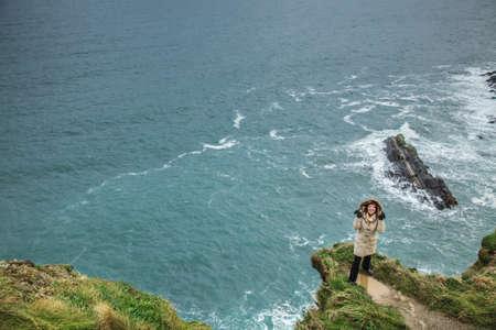 co cork: Irish atlantic coast. Woman tourist standing on rock cliff by the ocean Co. Cork Ireland Europe. Beautiful sea landscape natures beauty. Stock Photo