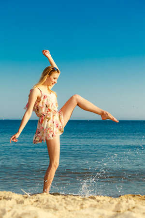 Vacation. Girl in summer dress splashing water on the coast. Young woman having fun relaxing on the sea. Summertime. photo