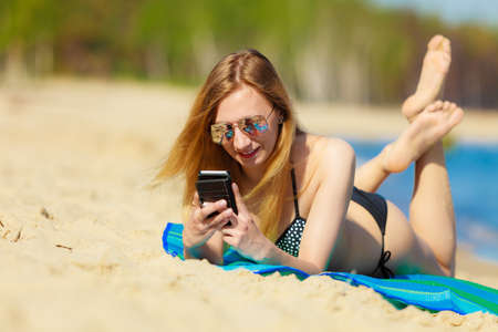 Summer vacation. Sexy girl in bikini sunbathing tanning on the beach. Young woman relaxing with mobile phone on the sea coast. Summertime. photo