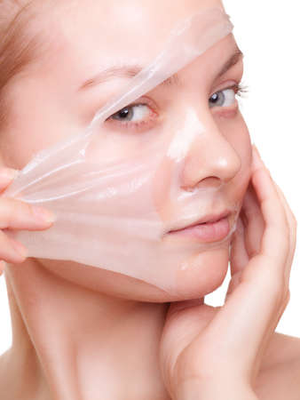 Portrait of girl young woman in facial peel off mask isolated on white  Peeling  Beauty and body skin care  Studio shot