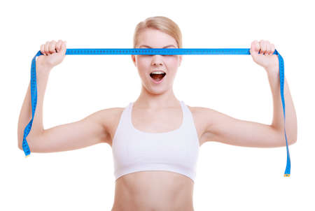 Body care diet weight loss concept Fitness girl sporty woman\ covered her eyes with blue measuring tape face expression isolated\ on white background